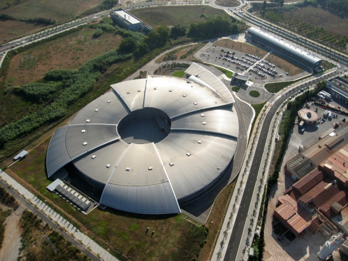 "Aerial view of the ALBA Synchrotron. The rounded part of the building (the ""eye"") is where the electron accelerators and beamlines are located."